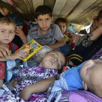 Iraqis fleeing violence in the province of Nineveh arrive in the province of Sulaimaniya on Friday. | REUTERS