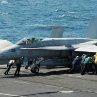 Sailors guide an F/A-18C Hornet on the aircraft carrier USS George H.W. Bush in the Persian Gulf on Friday in this handout image. Two Hornets conducted an airstrike Friday against Islamic State artillery that was being used against Kurdish forces defending the city of Irbil in northern Iraq. | REUTERS