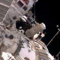 Spacewalking astronauts release baby satellite