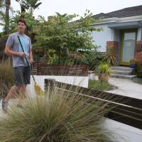 Rick Blankenship on Aug. 8 shows the drought-friendly front yard of his Long Beach, California home. As Californians face a historic drought, more people are tearing out thirsty grass lawns to cut down on water use. | AP