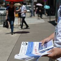 A volunteer on Sunday hands out flyers to people to raise awareness of an unofficial referendum in Macau. Voting began the same day in an unofficial referendum on the gambling enclave's electoral system, an action seen as a challenge to Beijing's authority in the semi-autonomous territory. | AFP-JIJI