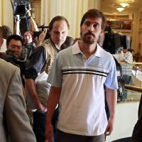 U.S. journalist James Foley (front) arrives at a hotel in Tripoli after being released by the Libyan government in May 2011. Islamic State militants posted a video Tuesday showing Foley being beheaded in retaliation for U.S. airstrikes in Iraq. | REUTERS