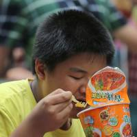 A Chinese boy eats instant noodles in the waiting lounge at the south train station in Beijing on Sunday. | AP