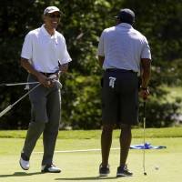 U.S. President Barack Obama laughs after Ahmad Rashad made a putt on the first green at the Farm Neck Golf Club in Oak Bluffs, Massachusetts, on Saturday. Obama is vacationing on the island for two weeks. | BLOOMBERG