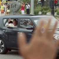 Pope Francis waves from a Kia Soul compact after his arrival in Seongnam, South Korea, Thursday. He called later for renewed efforts to forge peace on the war-divided Korean Peninsula and for both sides to avoid 'fruitless' criticisms and shows of force, opening a five-day visit to South Korea with a message of reconciliation as the North fired several projectiles into the sea. | AP
