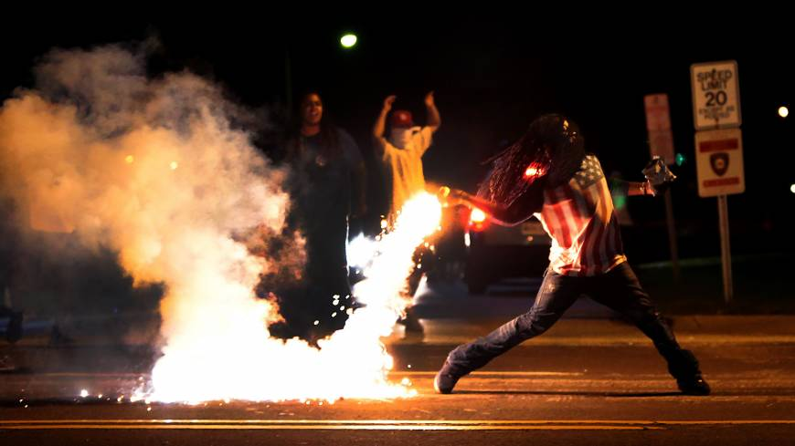 A demonstrator hurls a tear gas container back at tactical officers working to break up a group of bystanders in St. Louis on Wednesday. Unrest has vied with calls for calm in a suburb where an unarmed black teenager was shot dead by police.