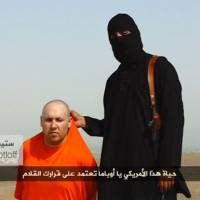 A masked Islamic State militant speaks beside U.S. journalist Steven Sotloff, who had gone missing in Syria nearly two years ago, at an unknown location in this still image from an undated video posted on a social media website. | REUTERS