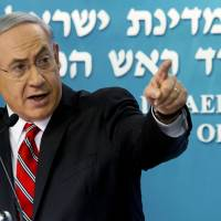 Israeli Prime Minister Benjamin Netanyahu points at a video screen showing Hamas militants firing rockets into Israel during a news conference in Jerusalem on Aug. 6. The prime minister has attempted to win support for military activity in the Gaza Strip by linking the group to Islamic State militants, whose brutal execution of U.S. journalist James Foley has drawn widespread condemnation. | AP