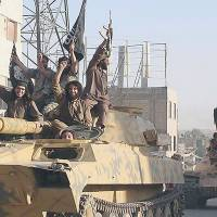 Fighters from the Islamic State group parade U.S.-made vehicles looted from the Iraqi Army in Raqqa, Syria, on June 30. As fears mount over the security threat posed by jihadis returning to the U.S., law enforcement officials have stepped up their efforts to identify individuals with links to the Sunni militant group.  | AP