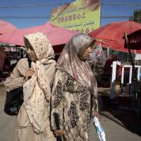 Uighur women in loose, full-length garments and headscarves associated with conservative Islam visit a market in Alaqagha in western China's Xinjiang province in July. | AP