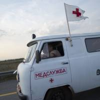 An ambulance rides in a convoy of white trucks carrying humanitarian aid as it passes along the main road M4 (Don highway)  of Russia's Voronezh region Tuesday.  Russia dispatched hundreds of trucks, although only a small proportion were counted in this convoy, covered in white tarps and sprinkled with holy water on a mission to deliver aid to a rebel-held zone in eastern Ukraine. | AP