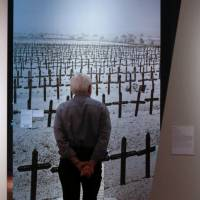 A visitor looks at a photo of a graveyard of soldiers on June 2, 2014, during an exhibition of World War I objects at the German Historical Museum in Berlin. On the left is the painting 'Armistice Day 1918' by U.S. artist Gifford Beal, and at right is the painting 'Insurrection' by German artist Hans Richter. | AP