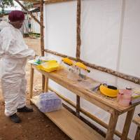 A health care worker prepares Ebola personal protective equipment before entering the Ebola isolation ward Tuesday at Kenema Government Hospital around 300 km from Freetown. The World Health Organization declared Tuesday, it is ethical for unproven drugs and vaccines to be used amid the unprecedented outbreak in West Africa, however it didn't address who should get the limited amount of drugs available and cannot predict the result of using untested drugs. | AP