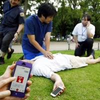 Dr. Kensuke Igarashi massages the heart of a test subject after receiving an SOS via a smartphone app and rushing to give aid during a trial exercise June 29 in Ueno Park in Tokyo. | KYODO