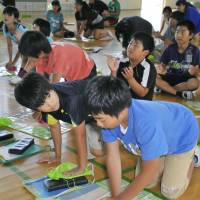 Sixth-graders learn how to provide heart massage during a training program on resuscitation techniques July 17 at an elementary school in the city of Saitama.   KYODO