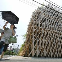 Women walk by Sunny Hills, aka the 'Pineapple House,' designed by Kengo Kuma, in Tokyo in mid-July. | AP