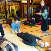 Buddhist priest Issho Fujita instructs participants in a Zen mediation workshop at Sougakuji, a Buddhist temple in Nagoya, in late April. | KYODO