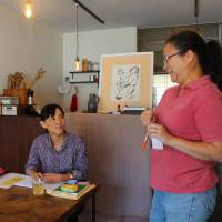 Ami Takahashi (left), head of Yuzuriha, a consultation center for former residents of children's institutions, in Koganei, west Tokyo, chats with a staff member on July 31. | MASAAKI KAMEDA