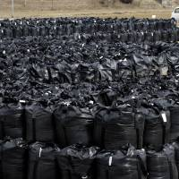 Radioactive waste packed in protective storage bags waits at a temporary storage site in Naraha, Fukushima Prefecture, in March 2013. | AP