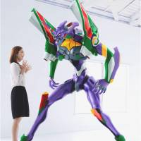 A woman stands next to a 2-meter sculpture of Evangelion Unit 01. Seven-Eleven Japan took orders Thursday for 25 of the figures, which cost ¥1.83 million each, selling out in two minutes. | KHARA INC.