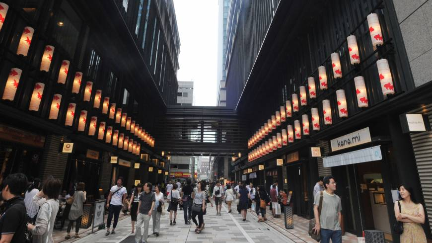 Shoppers stroll through the middle of the complex, illuminated by lanterns decorated with goldfish, on July 20.