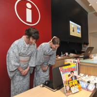 Alia Carter (left) from the United States and Paloma Free from Spain welcome foreign tourists at Coredo Muromachi's information counter in Tokyo's Nihonbashi district on July 19.   YOSHIAKI MIURA