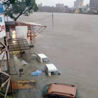 Vehicles are seen submerged in Kochi after heavy rains from Typhoon Halong flooded parts of the city this morning. | KYODO