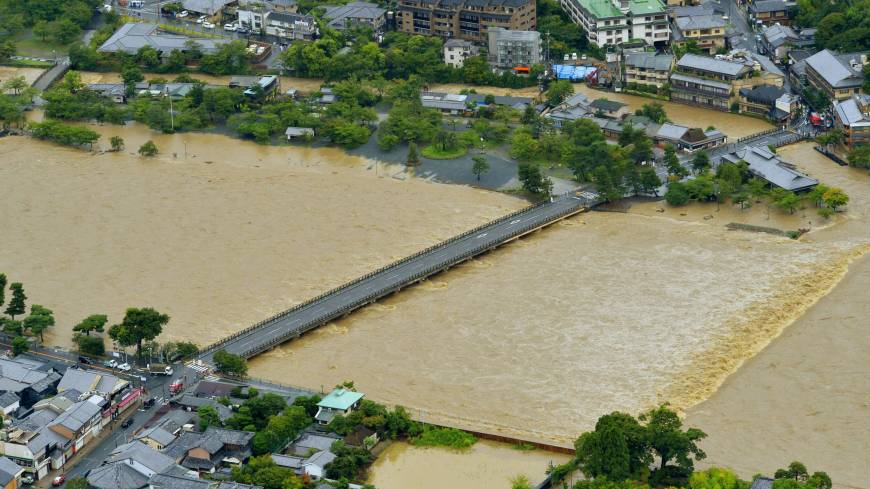 The Katsura River floods the Arashiyama district on the western outskirts of Kyoto Sunday following the heavy rains of Typhoon Halong.