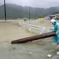A worker removes part of a tree trunk from a road in Shingu, Wakayama Prefecture, on Sunday after Typhoon Halong flooded the nearby Kumano River. | KUMANO SHIMBUN/KYODO