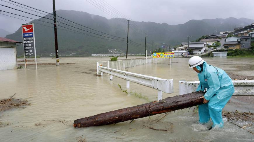 A worker removes part of a tree trunk from a road in Shingu, Wakayama Prefecture, on Sunday after Typhoon Halong flooded the nearby Kumano River.