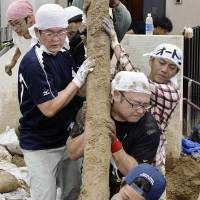 Volunteers clear debris Saturday morning from a residential area in Asaminami Ward, Hiroshima, that was devastated by mudslides last week.   KYODO