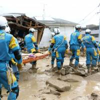 Police hunt for people missing Wednesday morning in the Asaminami district of Hiroshima after torrential rains triggered flooding and landslides on the outskirts of the city. | KYODO