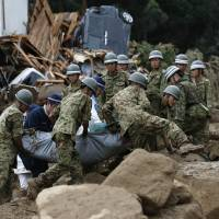 Self-Defense Forces personnel, assisted by police officers, carry a body from the site of a landslide that ripped through a residential area of Asaminami Ward, Hiroshima, on Wednesday, killing at least 36 people, including several children. | REUTERS