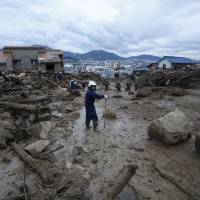 Police officers and Self-Defense Forces personnel search Asaminami Ward on the outskirts of Hiroshima for survivors of multiple landslides that killed 39 people and left 51 more missing on Wednesday following torrential rainfall. | REUTERS