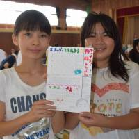 Hiroyo Miyamoto (left) and Yuna Michigami hold the handwritten newspaper they created at Bairin Elementary School in Asaminami Ward, Hiroshima, on Monday. Copies of the paper have been enlarged and put up on walls at the school, which is used as an evacuation shelter. | KYODO