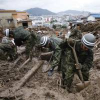 Self-Defense Force soldiers continue searching for survivors at a site where a landslide swept through a residential area in Asaminami Ward, Hiroshima, on Friday.   REUTERS