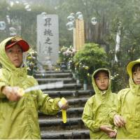 Children release bubbles Tuesday at a monument on Osutaka Ridge in Gunma Prefecture where JAL Flight 123 crashed. Mourners trekked there in heavy rain on the 29th anniversary of the accident. | KYODO