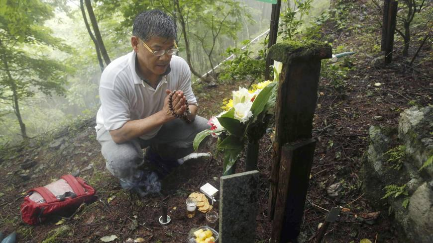 Masayuki Teranishi, 52, who lost his younger brother, Masatsugu, when Japan Airlines Flight 123 went down on Aug. 12, 1985, prays on a hillside at the crash site in Gunma Prefecture on Tuesday, the 29th anniversary of the world's worst single-plane disaster, which claimed 520 lives.