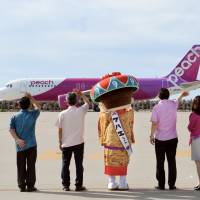 Workers at Peach Aviation wave as the low-cost carrier's first flight on the Naha to Fukuoka route prepares to depart from Naha Airport in Okinawa on July 19. | KYODO