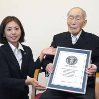 Sakari Momoi, 111, recognized as the world's oldest man by Guinness World Records, receives a certificate from a company representative on Wednesday in Tokyo. | KYODO