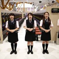Dynam employees practice their greeting messages during customer-care training ahead of the grand opening of a pachinko parlor in Fukaya, Saitama Prefecture, on July 29. | REUTERS