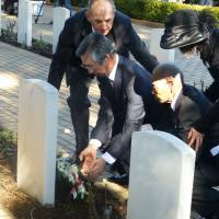 During an event held to mark the 70th anniversary of a massive breakout from a POW camp in Cowra on Aug. 5, 1944, former prisoner-of-war Teruo Murakami, 93, (third from left) lays flowers at a cemetery for Japanese soldiers who died in the incident. | KYODO