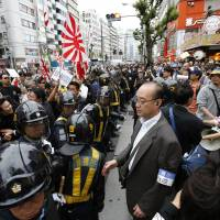 Nationalist protesters holding Hinomaru and Rising Sun flags march through a Tokyo street to denounce 'privileges' for Korean residents of Japan, as riot police look on in May 2013. | AP