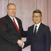 U.S. Deputy Secretary of Defense Robert Work shakes hands Friday with Ryota Takeda, parliamentary senior vice minister of defense, at the Defense Ministry before holding talks. | KYODO