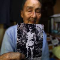 Former Imperial Japanese Army soldier Tokuro Inokuma, at his home in Yokosuka, Kanagawa Prefecture, shows a photograph of himself when he was 15 at an Imperial Japanese Army school in Mito, Ibaraki Prefecture, in 1944. | REUTERS
