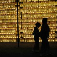 Paper lanterns provide the illumination during the annual Mitama Festival at Yasukuni Shrine in Tokyo on July 13. | REUTERS