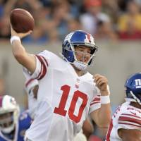 Back in action: Giants quarterback Eli Manning passes against the Bills during the Hall of Fame Game on Sunday. | AP