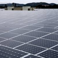 Here comes the sun: Solar panels sit at the SoftBank Takasago Solar Park in the city of Takasago, Hyogo Prefecture, in February. | BLOOMBERG