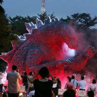 Native son: People gather to view a 6.6-meter-high model of Godzilla at Tokyo Midtown's garden in the capital's Akasaka neighborhood. | KYODO