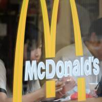 Customers sit behind the logo on a window of a McDonald's restaurant in Tokyo last week. | BLOOMBERG